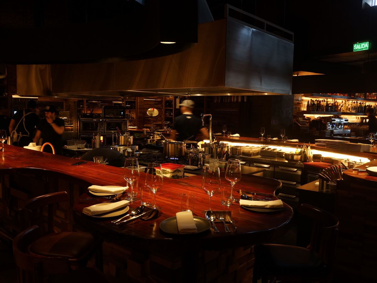 A chef's counter and place settings in a darkened bar