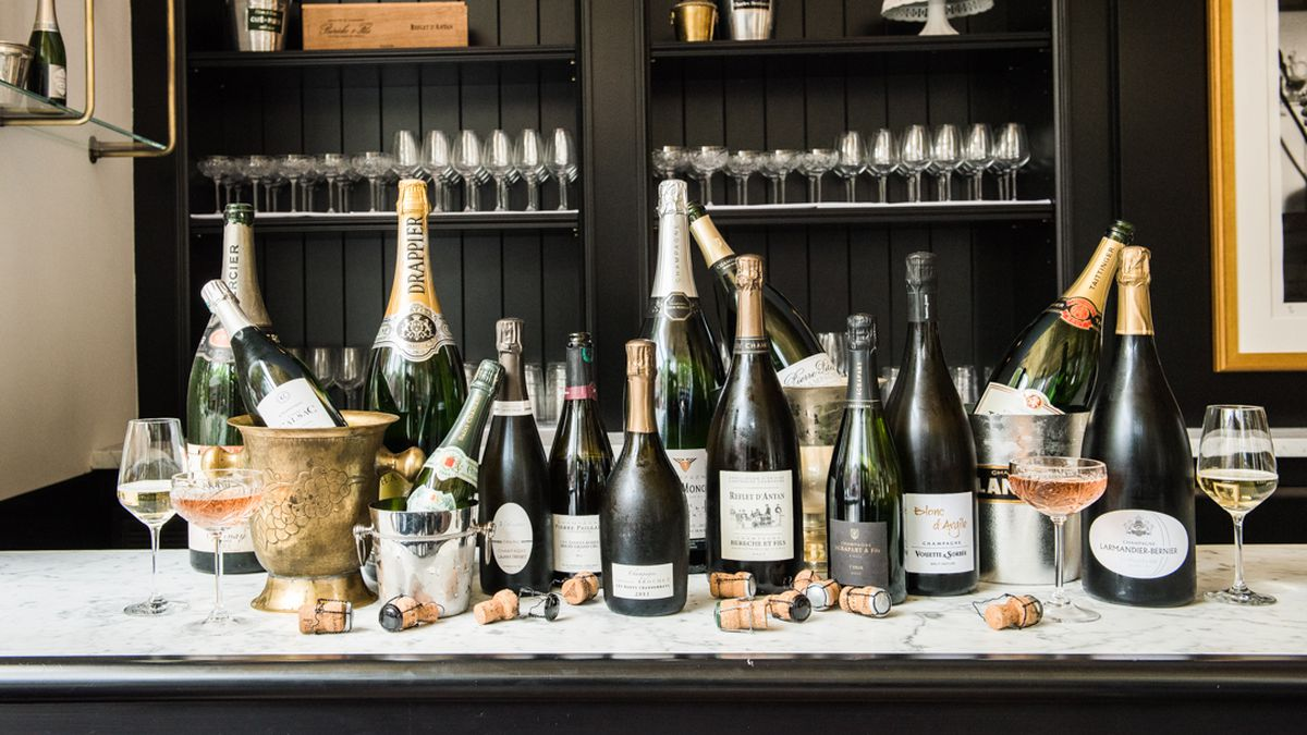 Champagne bottles and glasses of the wine sit on a bar