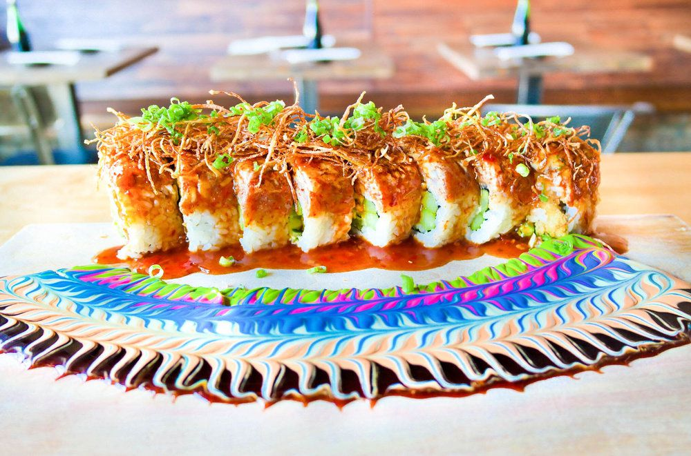 A maki roll plated with colorful sauces on the platter.