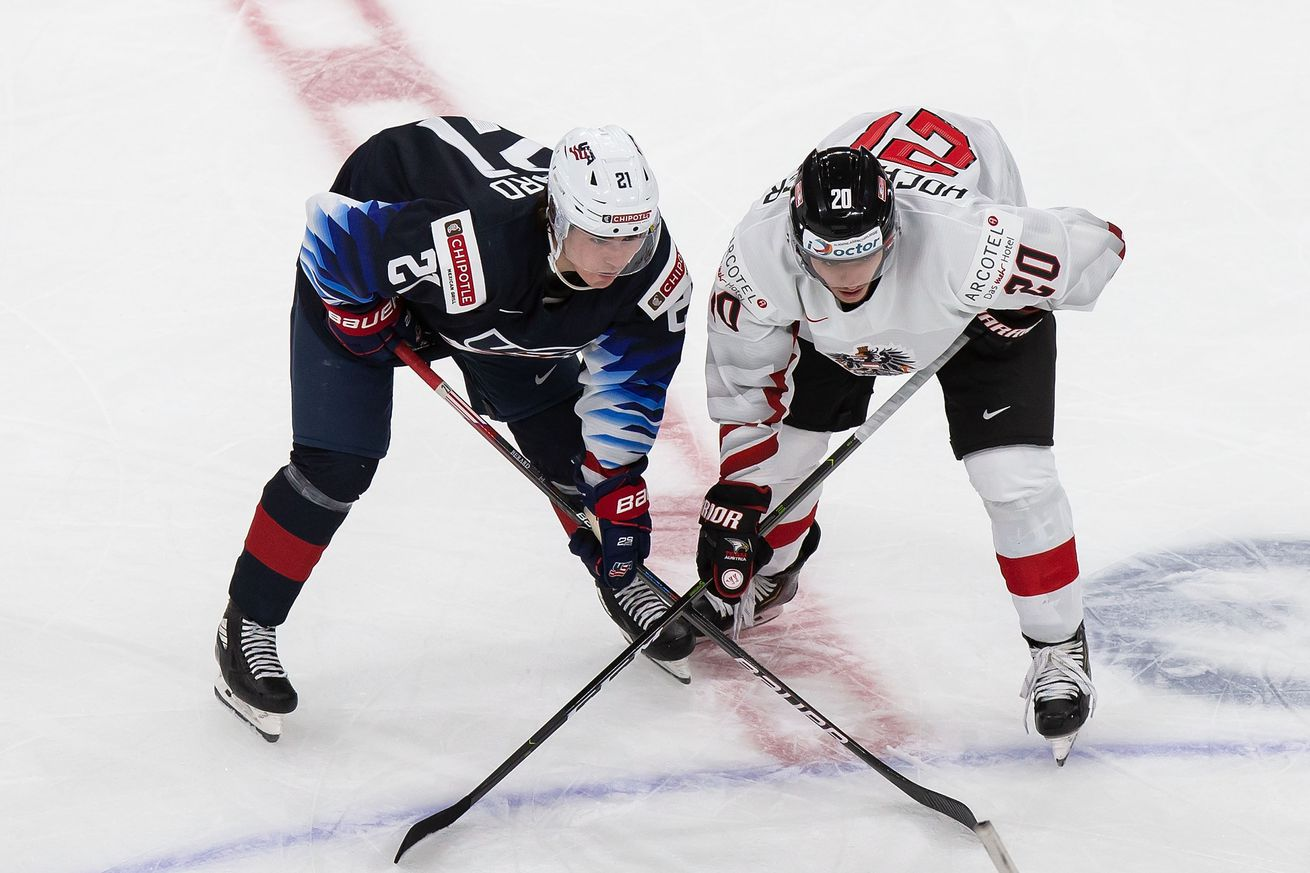 Brett Berard #21 of the United States lines up next to Fabian Hochegger #20 of Austria during the 2021 IIHF World Junior Championship at Rogers Place on December 26, 2020 in Edmonton, Canada.
