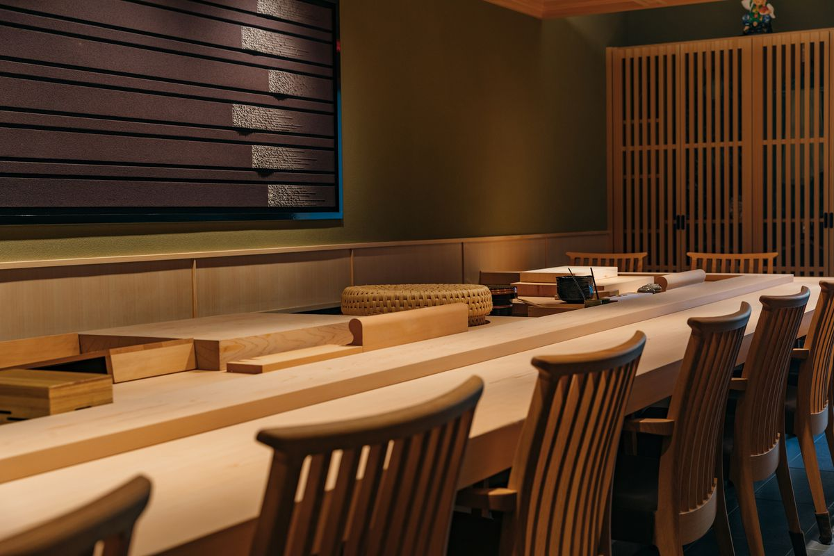 A wooden bare sushi counter with chairs lined at the counter.