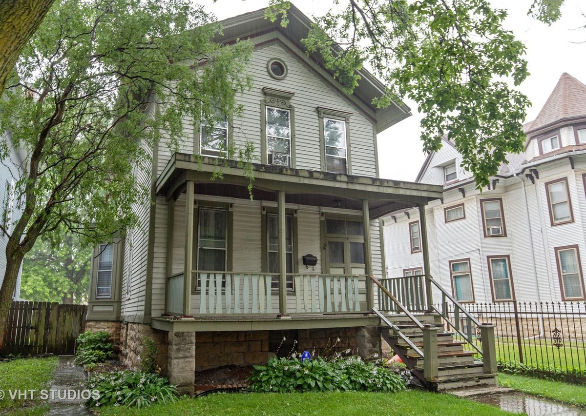The exterior of a historic two-story home with Victorian and Italianate features and a large front porch.