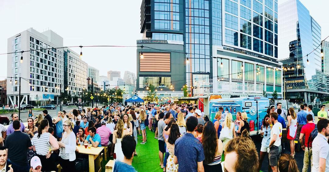 A crowded beer garden with skyscrapers in the background