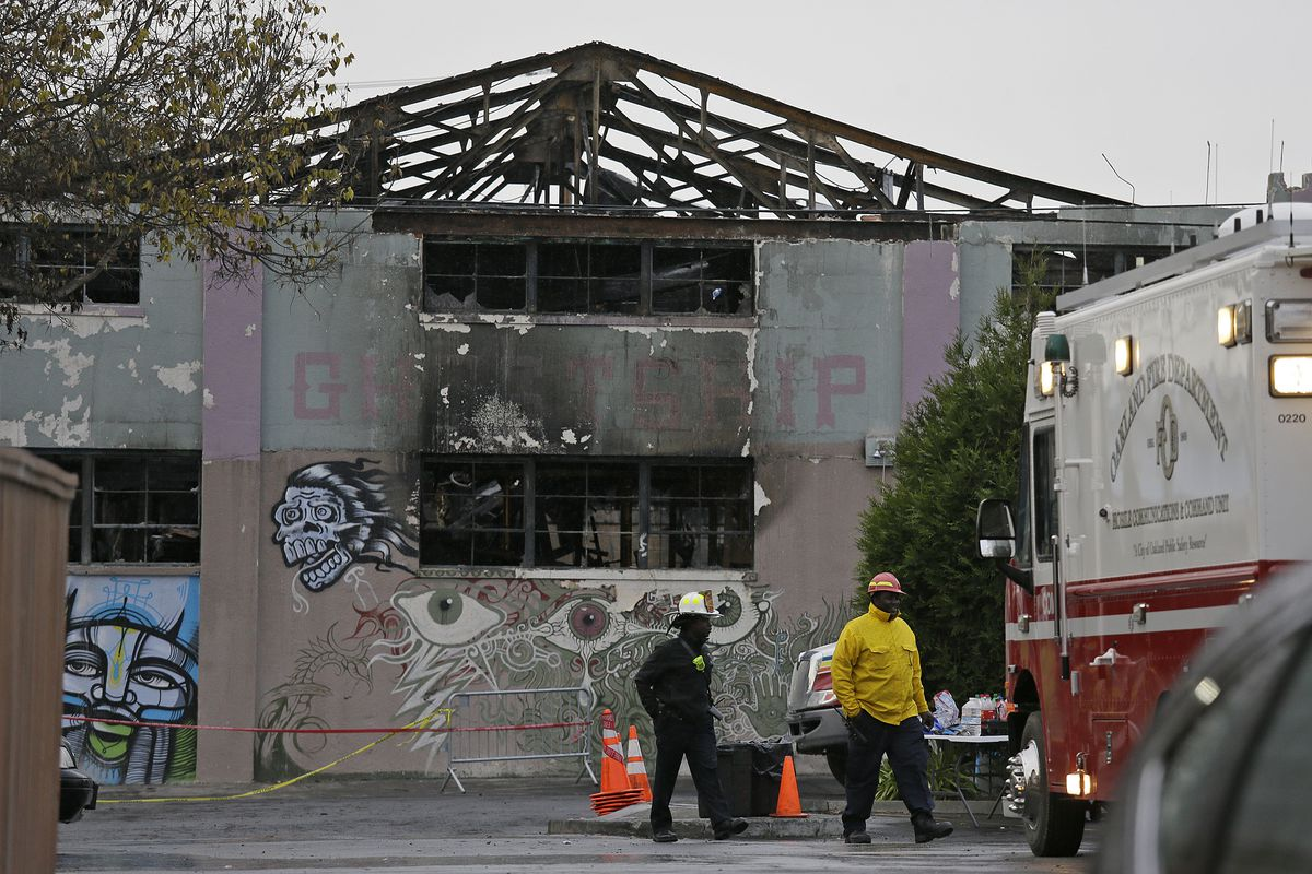 A pair of Oakland fire officials walk past the remains of the Ghost Ship warehouse fire.