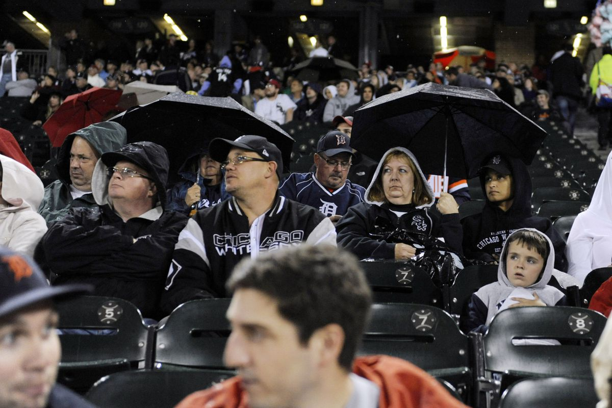 CHICAGO, IL - SEPTEMBER 13: People under umbrellas during a rain delay during a game between the Chicago White Sox and the Detroit Tigers on September 13,  2012 at U.S. Cellular Field in Chicago, Illinois. (Photo by David Banks/Getty Images)