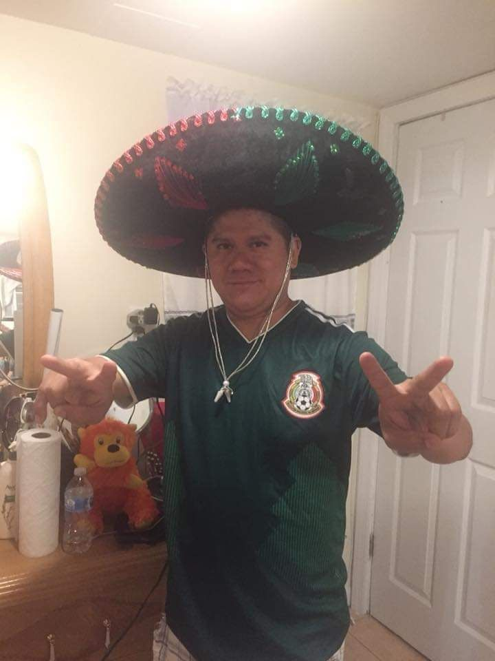Man wearing sombrero giving two peace signs with his hands.