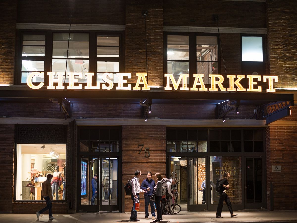 "A building with a sign that says ""Chelsea Market"" on an awning."