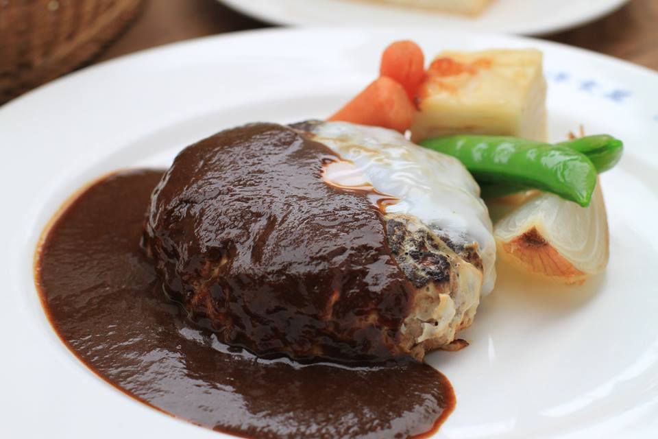 A hamburg steak patty covered in multiple sauces which pool around it on a white plate with a few cuts of cooked vegetables on the side in the background
