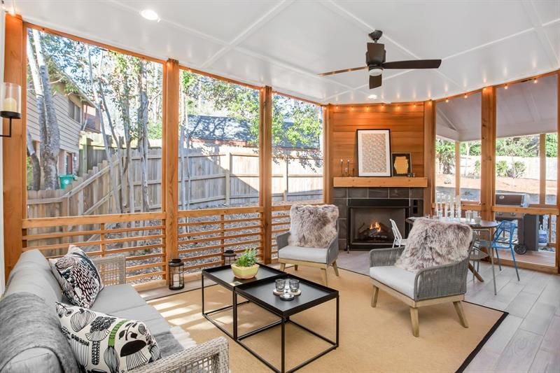 A screened-in lanai with a dramatic wood and stone outdoor fireplace.