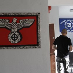 In this Thursday, April 26, 2012 photo a Nazi-style poster with a Celtic cross replacing the swastika is displayed on the wall, left, as Giorgos Germanis, right, a candidate of the extreme far-right Golden Dawn party and an unidentified man are seen at a party office in the suburban town of Artemis, 25 kilometers (15 miles) east of Athens. Reeling from a vicious financial crisis that has cost them pensions and jobs, Greeks have been turning away in droves from the mainstream politicians they feel have let them down.Firmly on the fringe of the right since it first appeared 20 years ago, Golden Dawn garnered a meager 0.23 percent in the 2009 elections. But its popularity has shot up over the past few months and support stood at about 5 percent in recent opinion polls, well above the 3 percent threshold needed to enter parliament.