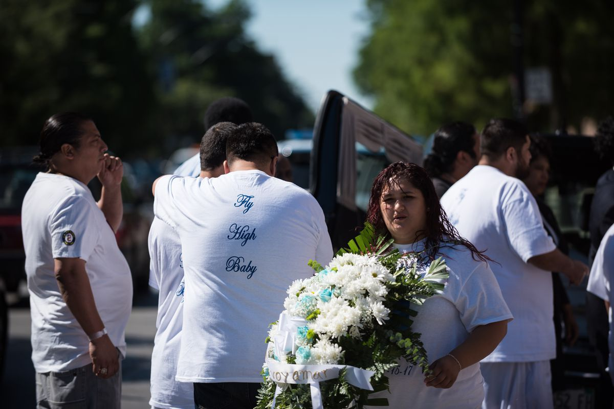 """Family and friends of 10-year-old Gustavo Garcia, who was shot and killed last Friday, gather around the hearse following his funeral service at Immaculate Conception Church. Many wore memorial T-shirts with the words """"Fly High Baby"""" on the back. 