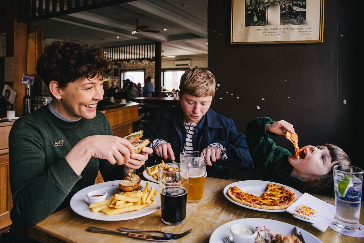 A young girl playfully munches pizza with her parents at a pub in Coburg