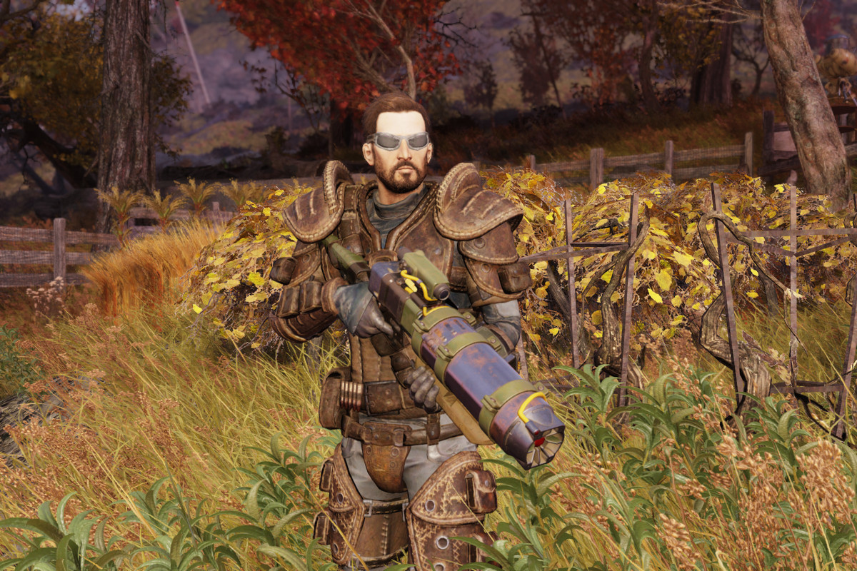 Fallout 76 - a player stands in a field, fully armed.