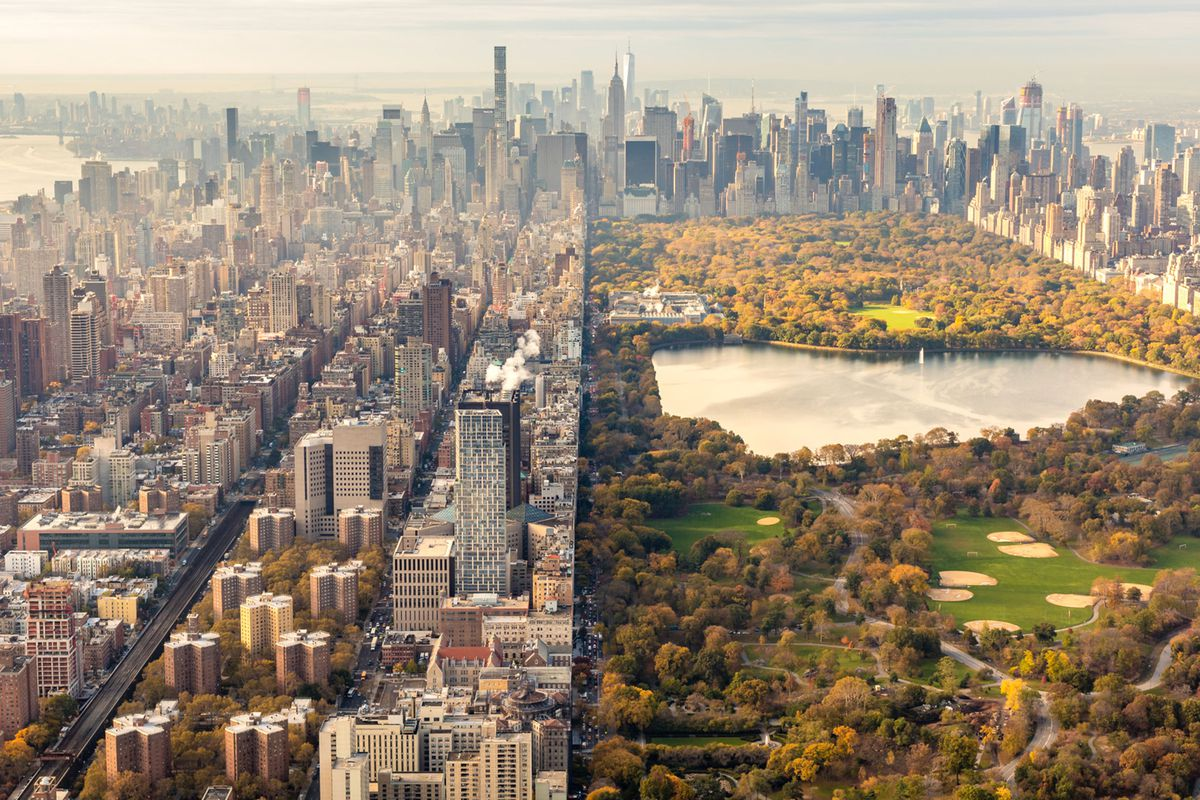 An aerial view of New York City. Central Park is surrounded by many skyscrapers and city buildings. The trees in Central Park are multicolored. It is Autumn.