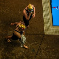 Swimmers walk past the races holding up masks at the 3A women's swimming state meet at the South Davis Recreation Center in Bountiful on Saturday, Feb. 13, 2021.