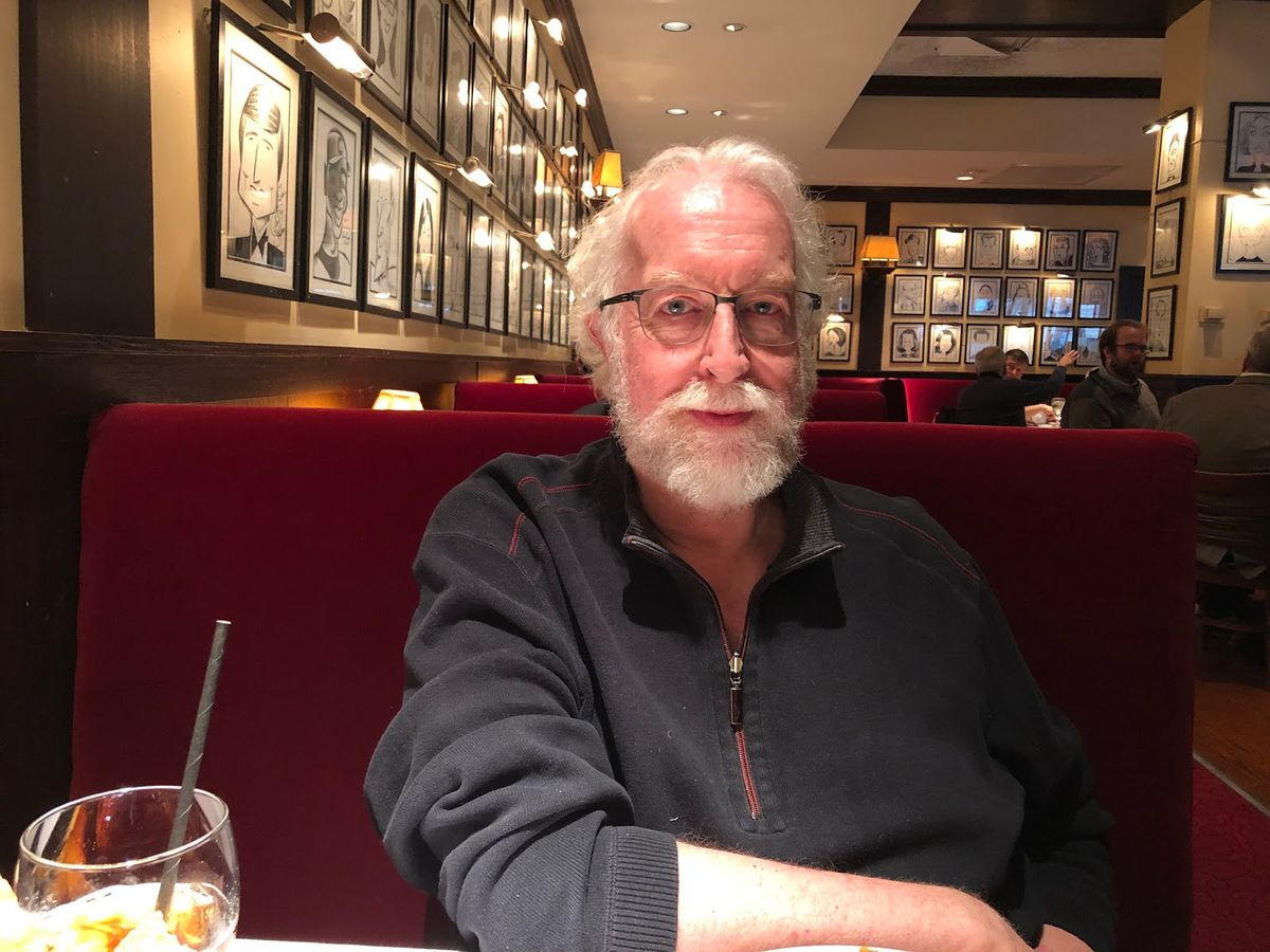 A white bearded man at a restaurant table.