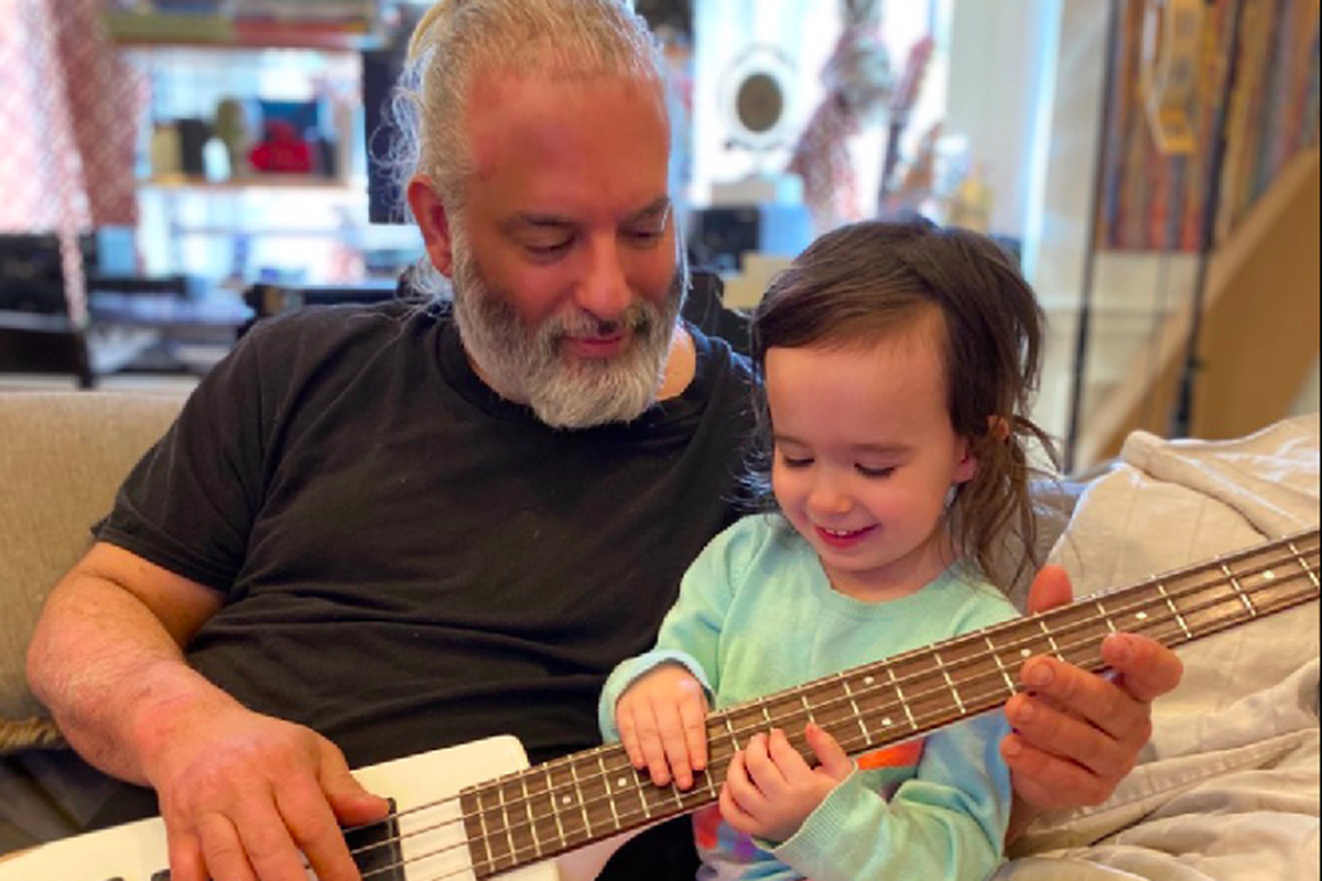 "Matthew ""Turk"" Agostini playing guitar with his 3-year-old daughter Violet."