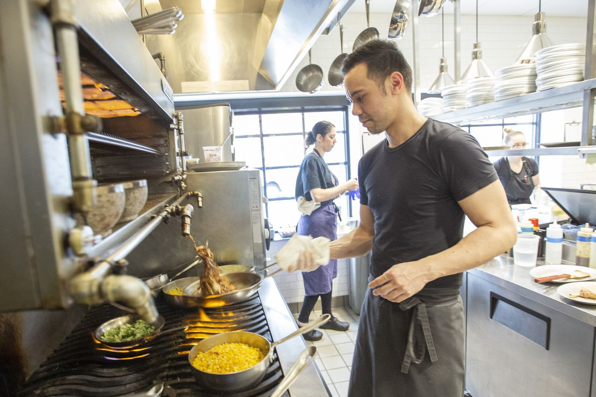 A male chef cooking at a stove in a restaurant kitchen.
