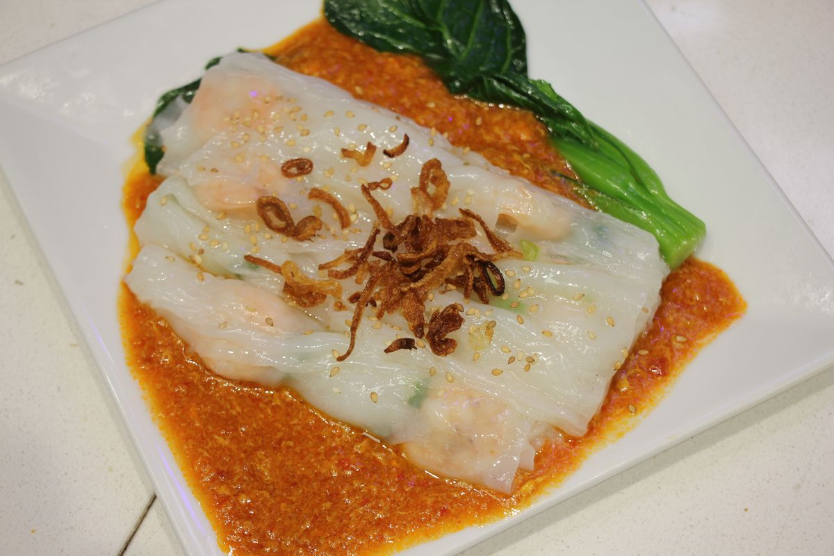 Several white rice rolls place on a white plate in a pool of orange sauce