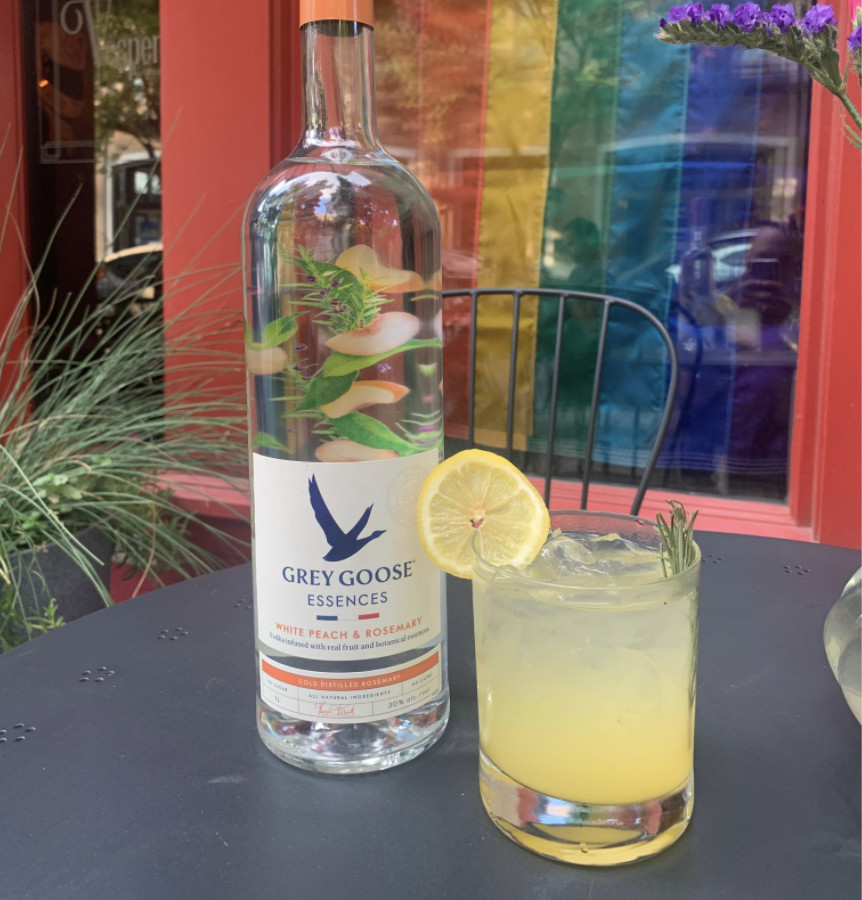 A light yellow cocktail in a low tumbler glass garnished with a round lemon slice in front of a Grey Goose Essences bottle