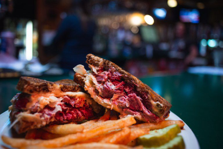 A Reuben sandwich sliced in half and stacked on a plate beside a pile of fries with a blurred bar in the background