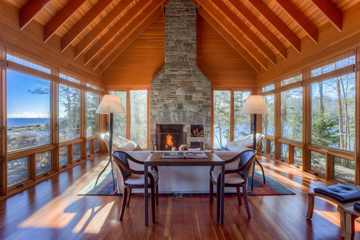 Interior of open-plan living room facing a stone fireplace and three walls of windows opening onto ocean views.