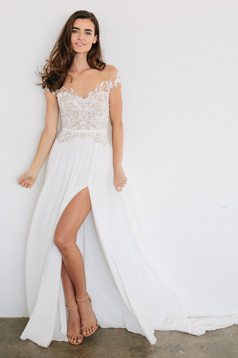 cf123685fe7 A model wearing a white wedding gown with a lace top and full skirt with a