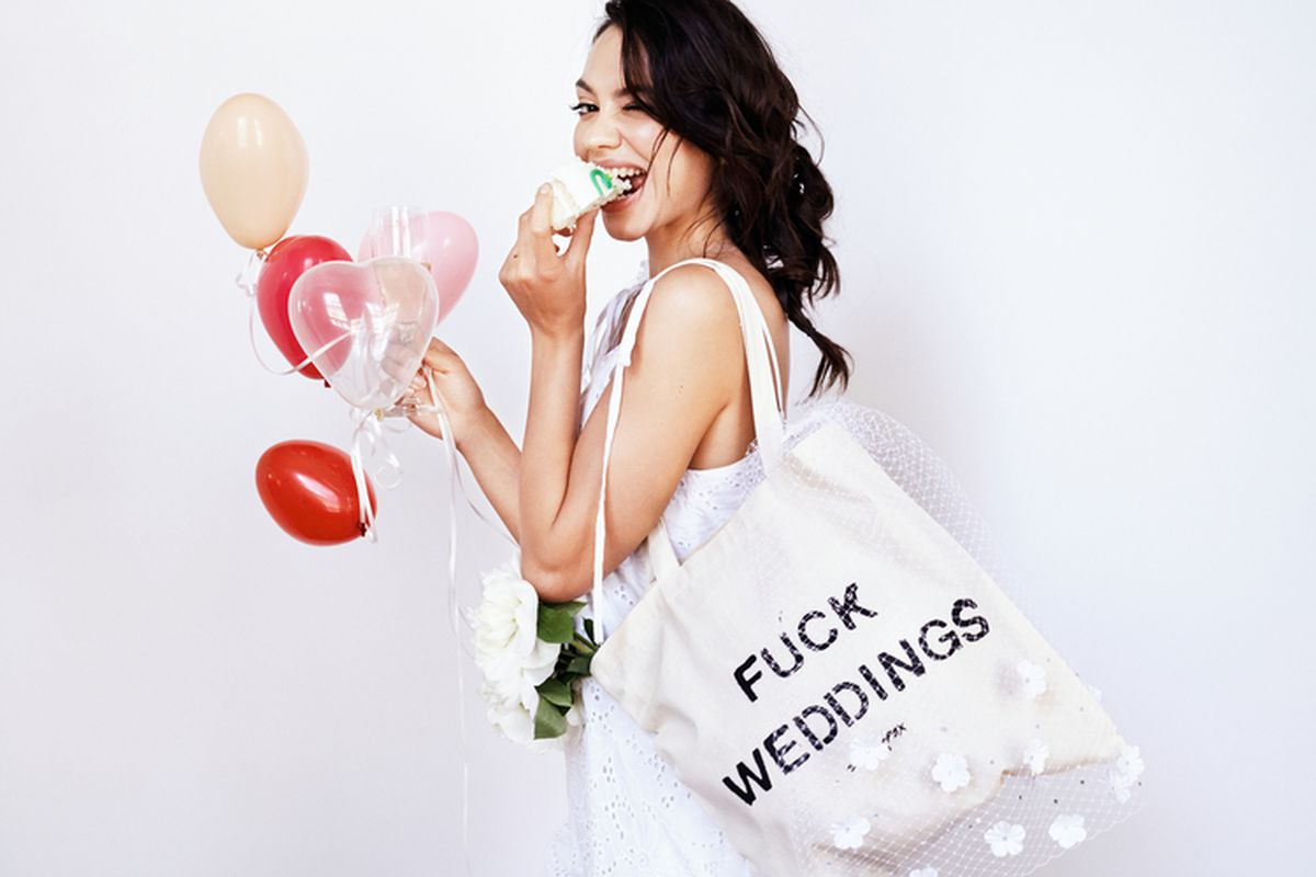 """A bride holding a tote bag that says """"Fuck Weddings"""""""