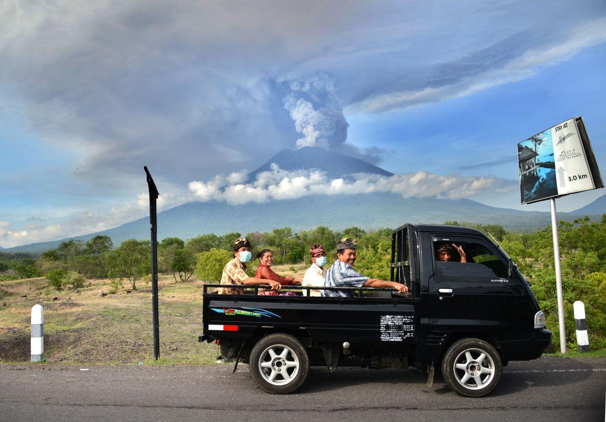 TOPSHOT - Balinese people ride on an open car past Mount Agung erupting seen from Kubu sub-district in Karangasem Regency, on Indonesia's resort island of Bali on November 27, 2017.