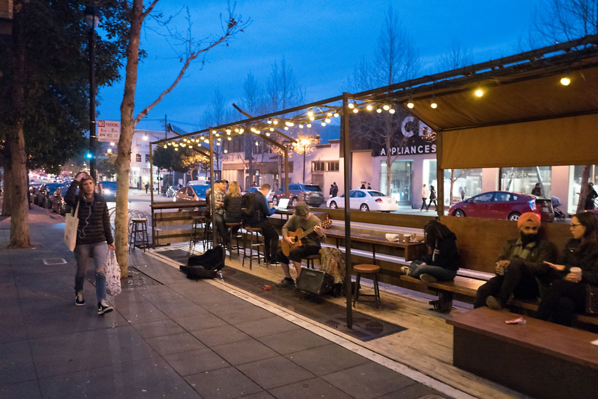 People walk past a public parklet where a street musician performs on Valencia street at dusk.