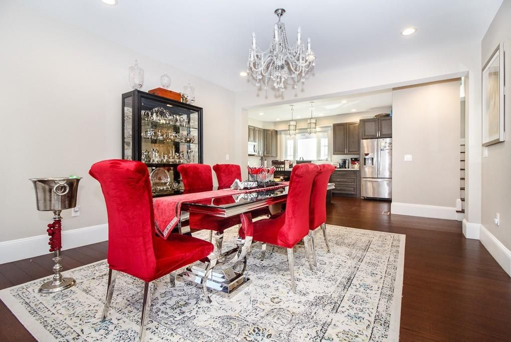 A spacious dining room with a long table with chairs, and there's a chandelier above.
