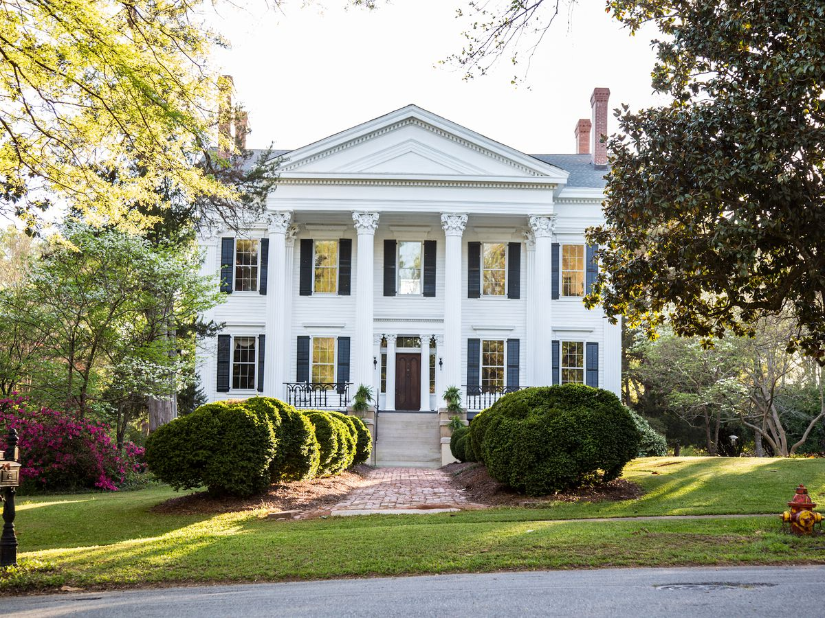 Two-story home with white columns, lots of windows, and a brick paver sidewalk leading to the front steps.