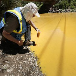 """FILE """""""" In this Aug. 6, 2015, file photo, Dan Bender, with the La Plata County Sheriff's Office, takes a water sample from the Animas River near Durango, Colorado, after the accidental release of an estimated 3 million gallons of waste from the Gold King Mine by a crew led by the U.S. Environmental Protection Agency. The EPA said Friday, Jan. 13, 2017, that it won""""™t pay claims totaling more than $1.2 billion for economic damages from the spill, saying the law prohibits it."""