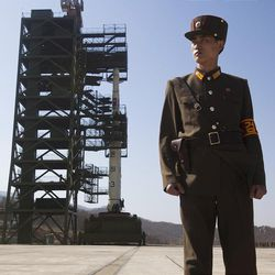 A North Korean soldier stands in front of the country's Unha-3 rocket, slated for liftoff between April 12-16, at Sohae Satellite Station in Tongchang-ri, North Korea on Sunday April 8, 2012. North Korean space officials have moved a long-range rocket into position for this week's controversial satellite launch, vowing Sunday to push ahead with their plans in defiance of international warnings against violating a ban on missile activity. (AP Photo/David Guttenfelder)