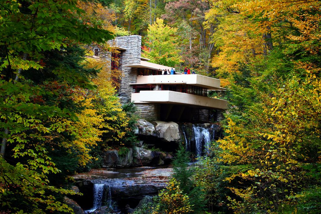 Fallingwater by Frank Lloyd Wright. The house has terraced portions. Under the house is a waterfall. The waterfall is surrounded by trees with multicolor leaves.