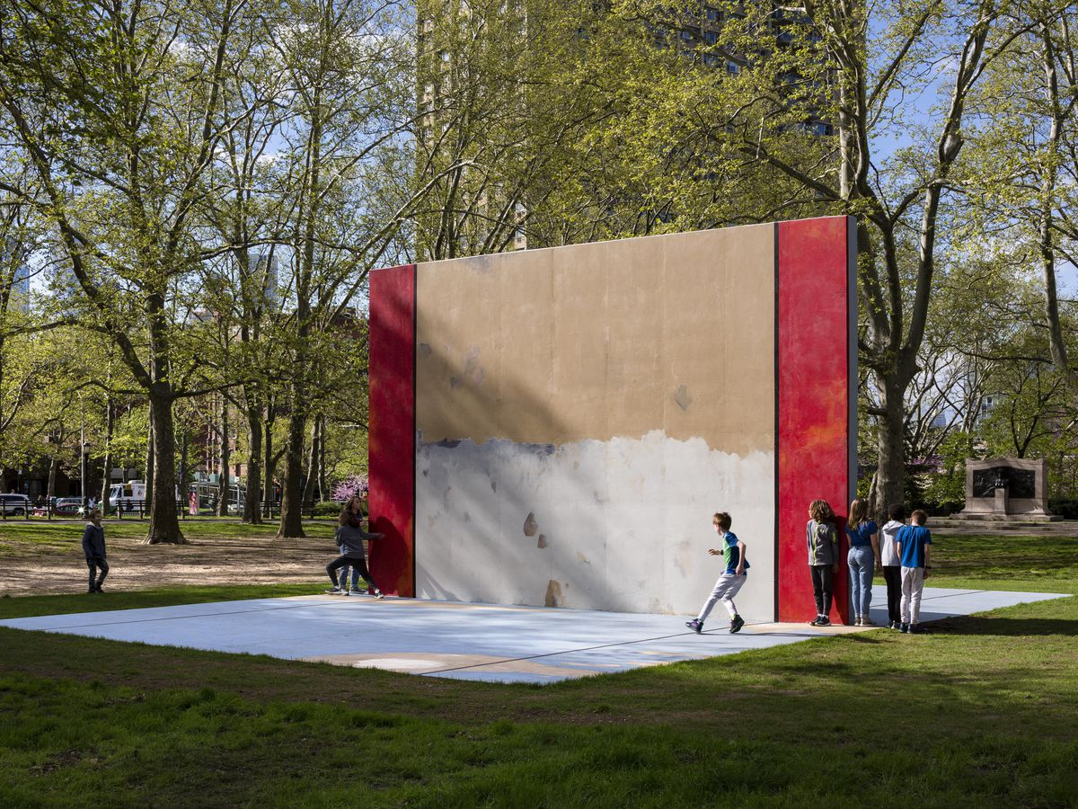 A structure similar to a handball court painted in white, red, and beige. Several individuals can be seen walking over it.
