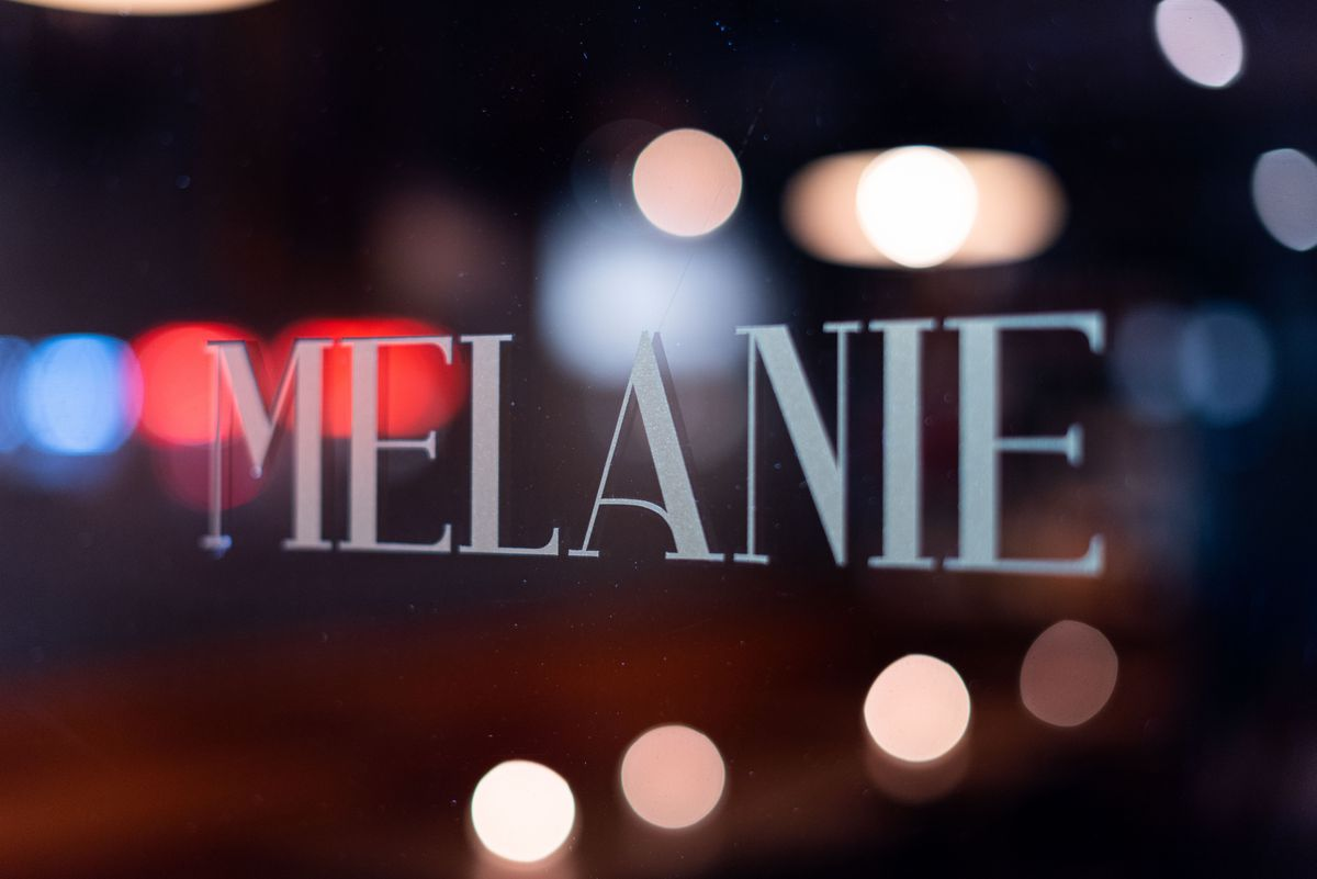 A sparkling sign for a wine bar with glowing city lights bouncing off the glass.