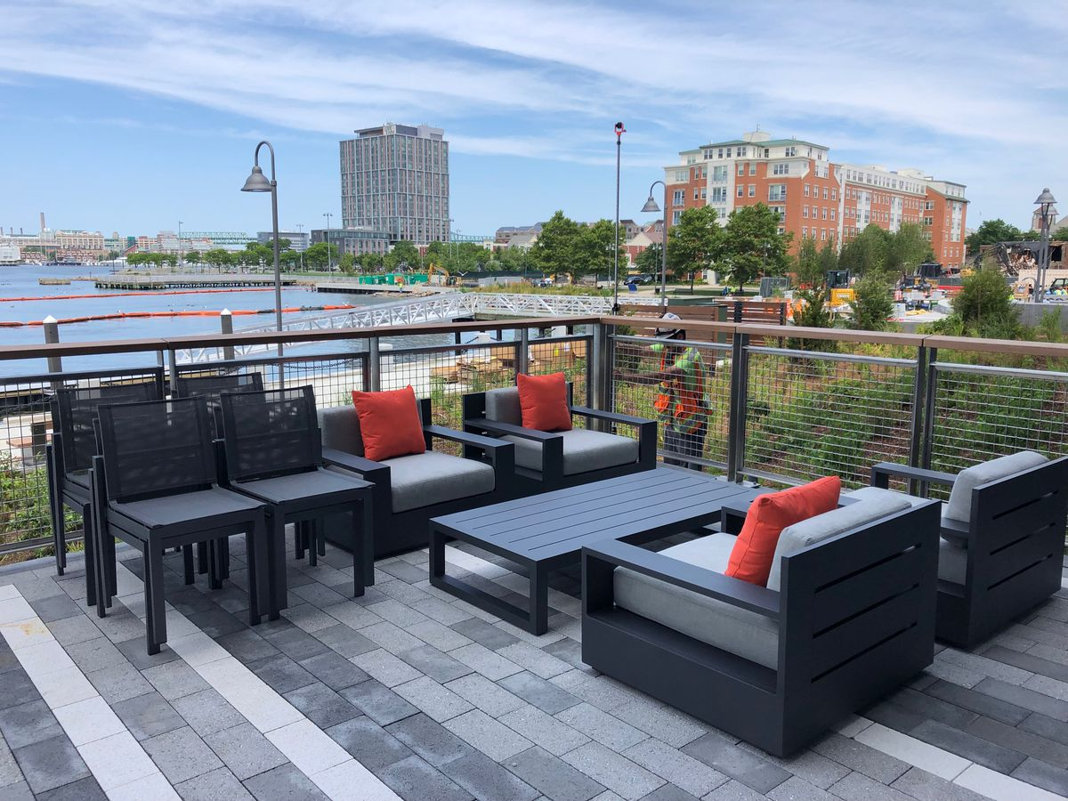 A terrace with a table and chairs overlooking a harbor.