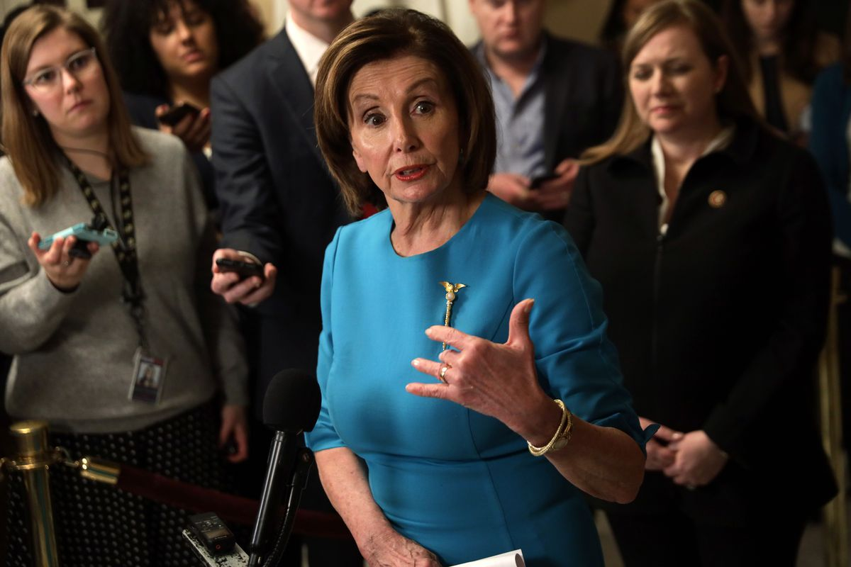 Pelosi, wearing her Mace of the Republic pin, gestures surrounded by reporters holding out their phones to record her comments.