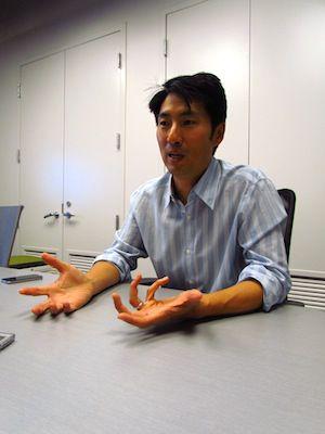 josh tsui sits at a desk