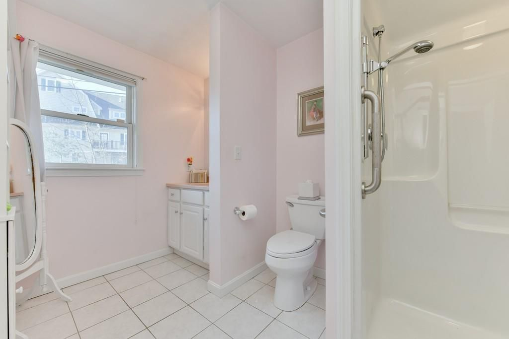 A bathroom with nothing across the shower.