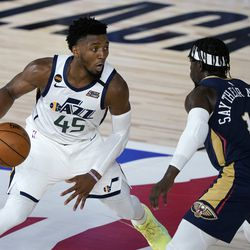 Utah Jazz's Donovan Mitchell (45) heads to the basket past New Orleans Pelicans' Jrue Holiday (11) during the second half of an NBA basketball game Thursday, July 30, 2020, in Lake Buena Vista, Fla. (AP Photo/Ashley Landis, Pool)