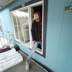 Israel Garcia is forced to exit his mobile home from a window after it was damaged in a 5.7 magnitude earthquake centered in Magna on Wednesday, March 18, 2020.