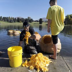 Kyle Fox cleans out a pumpkin to race as his son Kc watches as part of the 2013 Mountain Valley Seed Co. Ginormous Pumpkin Regatta at Sugarhouse Park on Saturday, October 19, 2013.