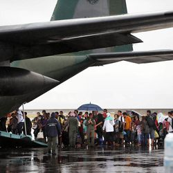 People line up to leave Tacloban, Friday, Nov. 22, 2013 on a military transport.