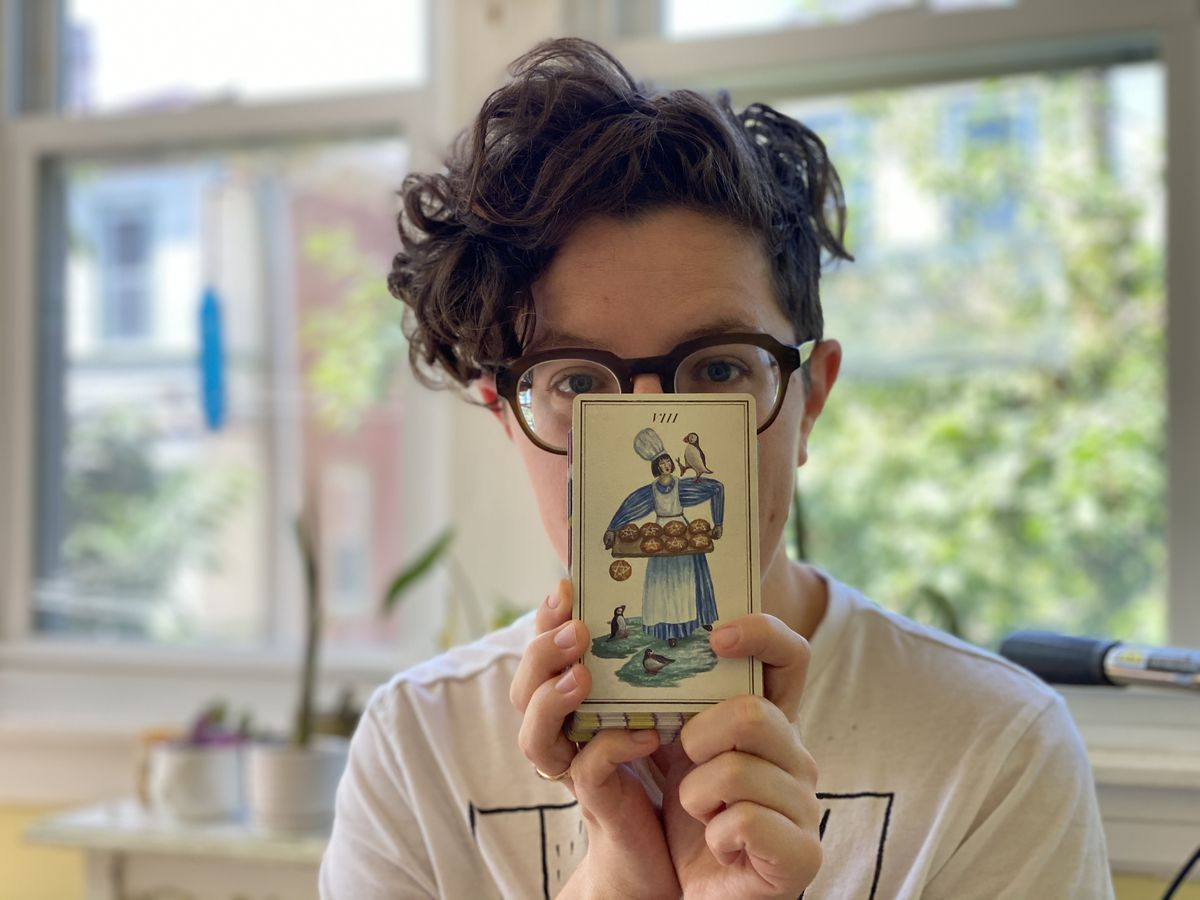 A woman holds a tarot card in front of her face
