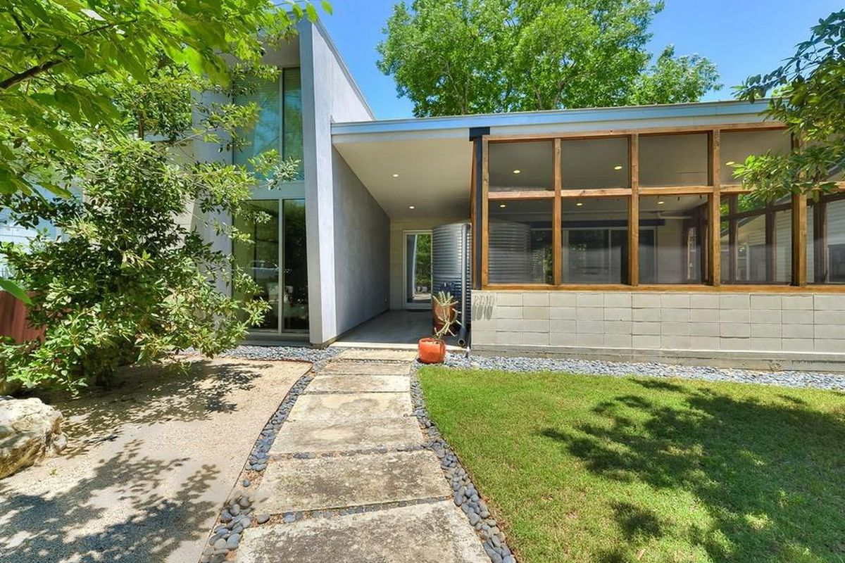 Rectangular modern/International-looking house with two wings, concrete, big window wall, tree