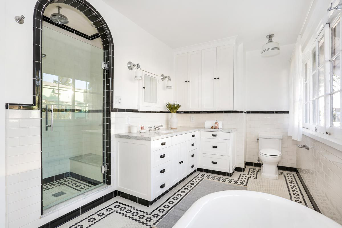 The bathroom is lined in black and white tile. There are white cabinets with gray marble countertops and black handle pulls.