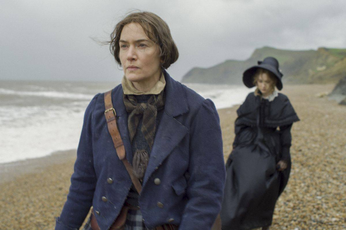 Kate Winslet walks ahead of Saoirse Ronan on a windblown beach in Ammonite