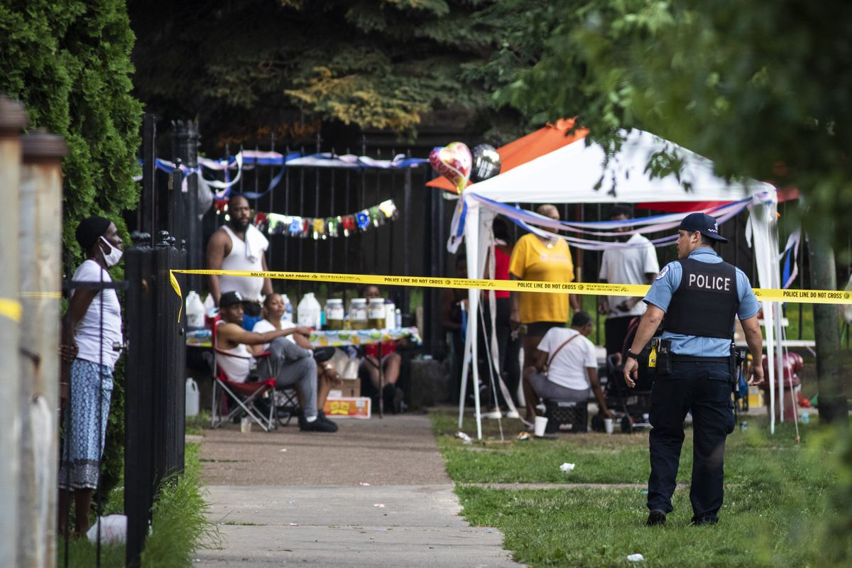 Residents enjoy a birthday party Wednesday evening while Chicago police investigate in the 2100 block of East 71st Street in South Shore, where three men were shot and wounded.